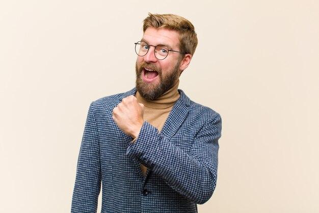 Jeune homme d'affaires blond se sentant heureux, positif et couronné de succès, motivé face à un défi