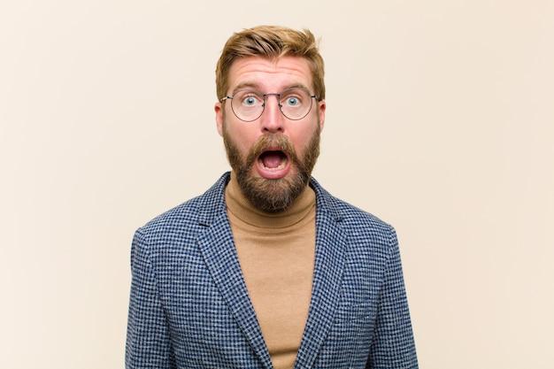 Jeune homme d'affaires blond se sentant terrifié et choqué, avec la bouche grande ouverte dans la surprise