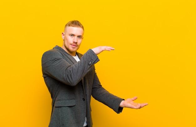 Jeune homme d'affaires blond tenant un objet avec les deux mains sur l'espace de copie latérale, montrant, offrant ou annonçant un objet