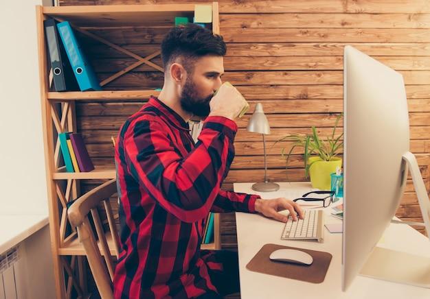 Jeune homme d'affaires, boire du café tout en travaillant sur pc