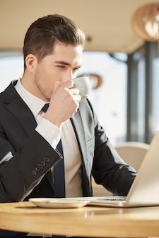 Jeune homme d'affaires, boire du café, travaillant sur son ordinateur au café