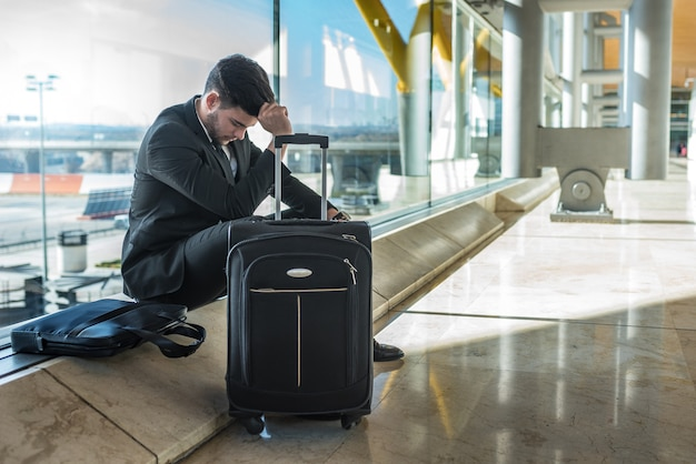 Jeune homme d'affaires bouleversé à l'aéroport en attendant son vol retardé avec des bagages