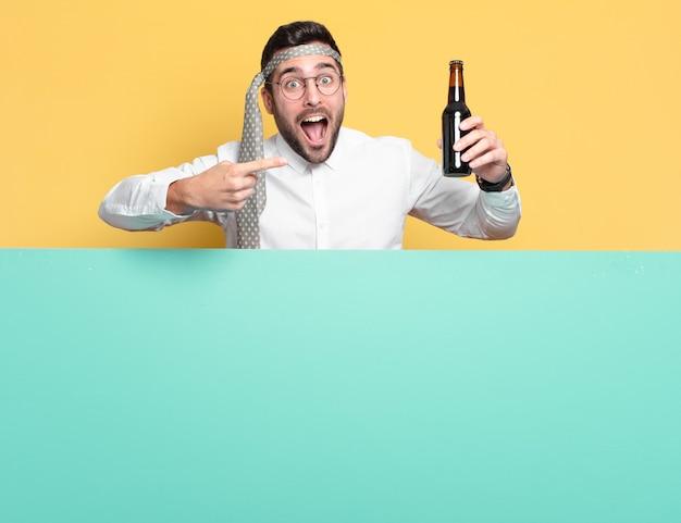 Jeune homme d'affaires avec une bouteille de bière célébrant de bonnes nouvelles