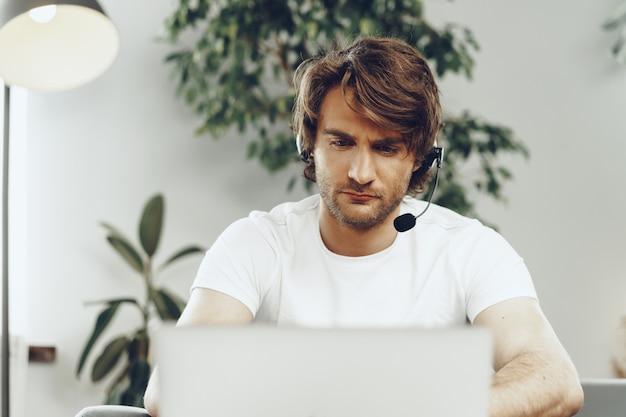 Jeune homme d'affaires avec un casque travaillant sur un ordinateur portable à la maison