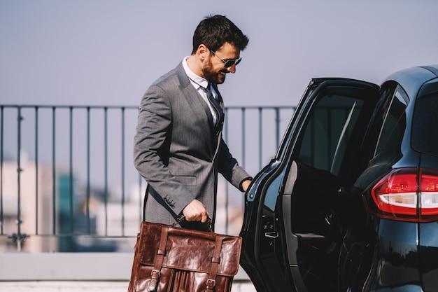 Jeune homme d'affaires caucasien barbu souriant en costume tenant une mallette et entrant dans sa voiture.