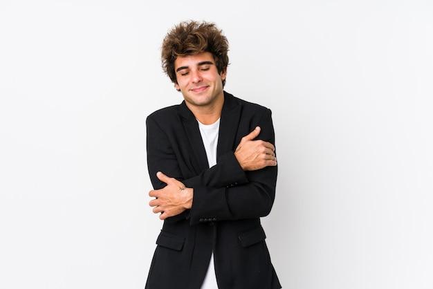 Jeune homme d'affaires caucasien contre un mur blanc isolé câlins, souriant insouciant et heureux.