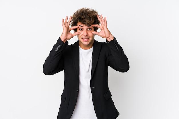 Jeune homme d'affaires caucasien contre un mur blanc isolé en gardant les yeux ouverts pour trouver une opportunité de réussite.