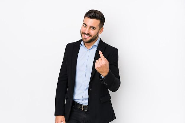 Jeune homme d'affaires caucasien contre un mur blanc isolé pointant avec le doigt sur vous comme si vous invitiez à vous rapprocher.