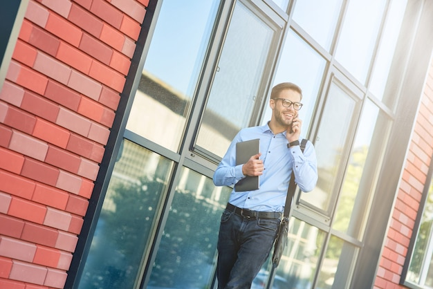 Jeune homme d'affaires caucasien heureux portant une chemise bleue et des lunettes tenant son ordinateur portable parlant par