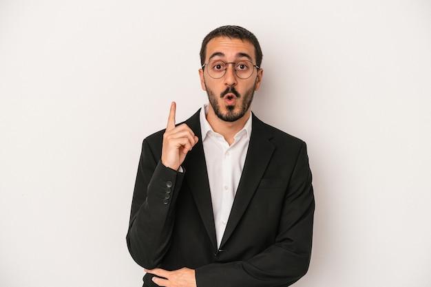 Jeune homme d'affaires caucasien isolé sur fond blanc ayant une bonne idée, concept de créativité.