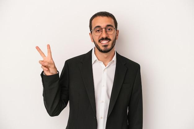 Jeune homme d'affaires caucasien isolé sur fond blanc joyeux et insouciant montrant un symbole de paix avec les doigts.