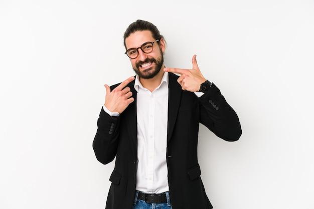 Jeune homme d'affaires caucasien isolé sur fond blanc sourit, pointant du doigt la bouche.