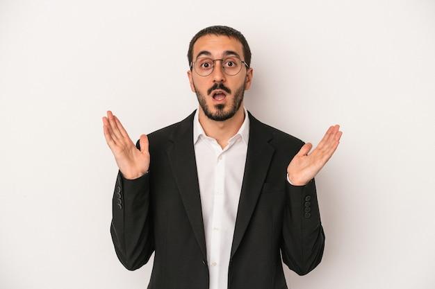 Jeune homme d'affaires caucasien isolé sur fond blanc surpris et choqué.