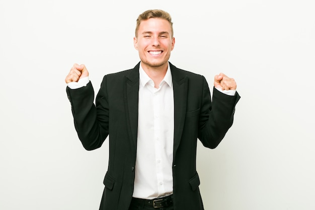 Jeune homme d'affaires caucasien levant le poing, se sentant heureux et réussi. concept de victoire.