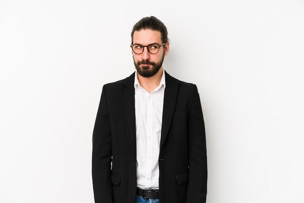 Jeune homme d'affaires caucasien sur un mur blanc, se sent douteux et incertain.