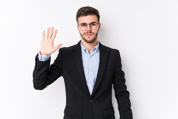 Jeune homme d'affaires caucasien posant dans un mur blanc jeune homme d'affaires caucasien souriant gai montrant le numéro cinq avec les doigts.
