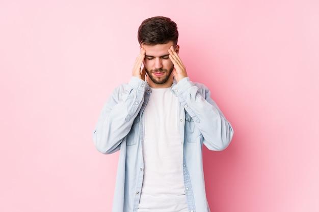 Jeune homme d'affaires caucasien posant dans un mur blanc touchant les temples et ayant des maux de tête