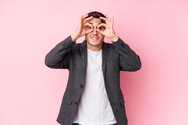 Jeune homme d'affaires caucasien posant isolé montrant signe correct sur les yeux