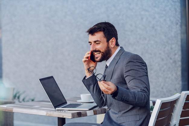 Jeune homme d'affaires caucasien positif en costume assis à table, tenant des lunettes et ayant un appel téléphonique avec sa femme. sur la table sont un ordinateur portable et du café.