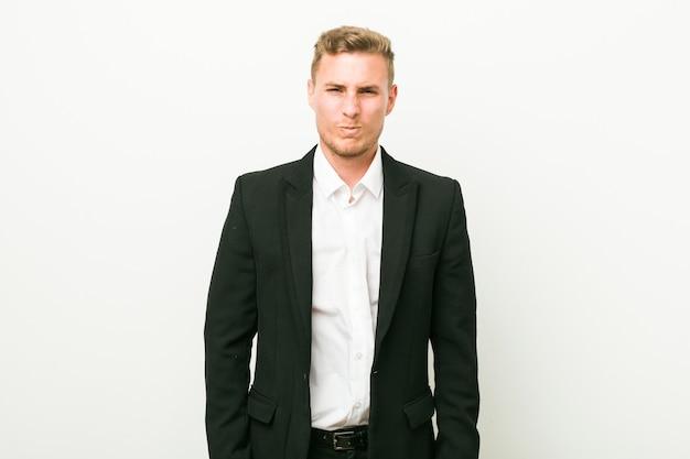 Jeune homme d'affaires caucasien souffle les joues, a une expression fatiguée