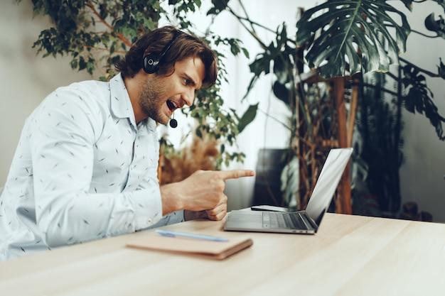 Jeune homme d'affaires caucasien tenant un appel vidéo avec des partenaires clients
