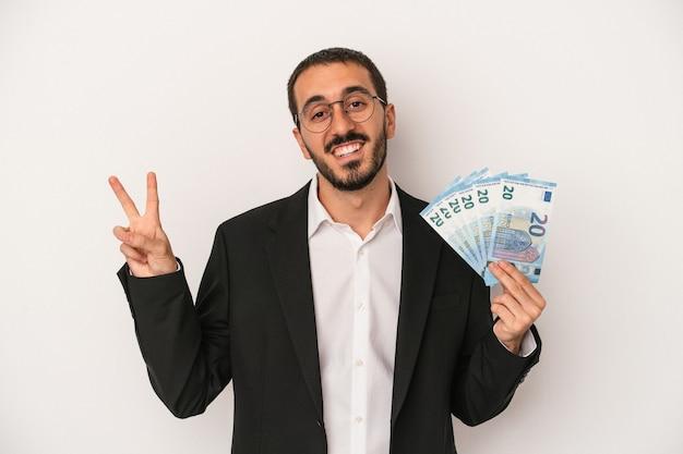 Jeune homme d'affaires caucasien tenant des billets isolés sur fond blanc joyeux et insouciant montrant un symbole de paix avec les doigts.