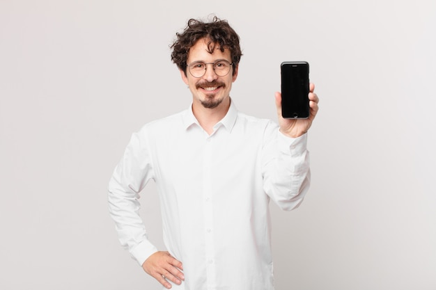 Jeune homme d'affaires avec une cellule souriant joyeusement avec une main sur la hanche et confiant