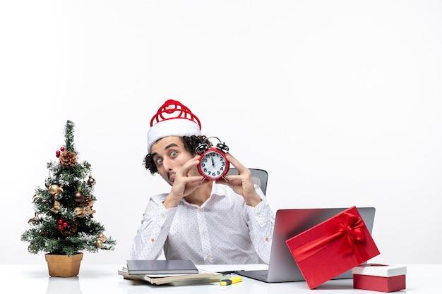 Jeune homme d'affaires avec chapeau de père noël et montrant l'horloge en regardant quelque chose de surprise et assis au bureau sur fond blanc