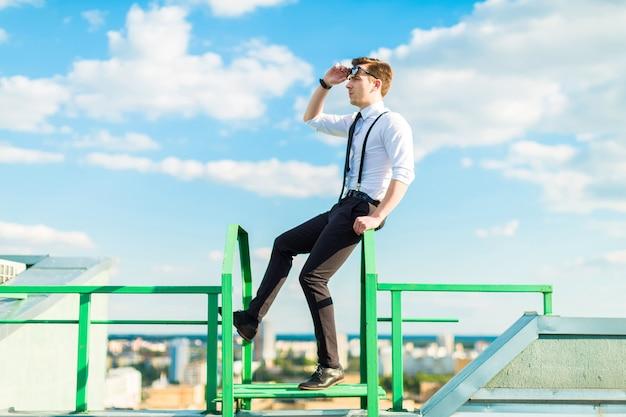 Jeune homme d'affaires en chemise blanche, cravate, bretelles et lunettes de soleil se tient sur l'échelle de toit
