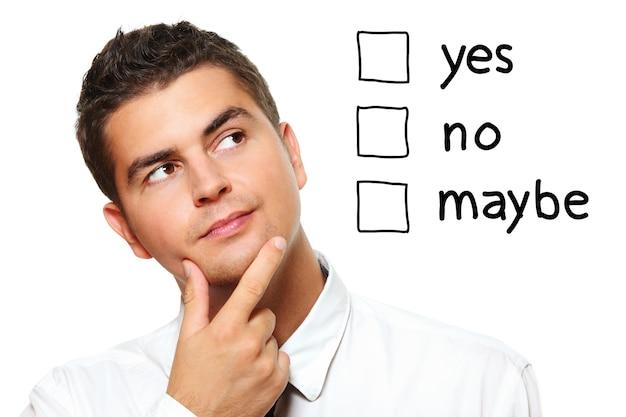 Un jeune homme d'affaires choisissant parmi trois options oui non peut-être sur fond blanc