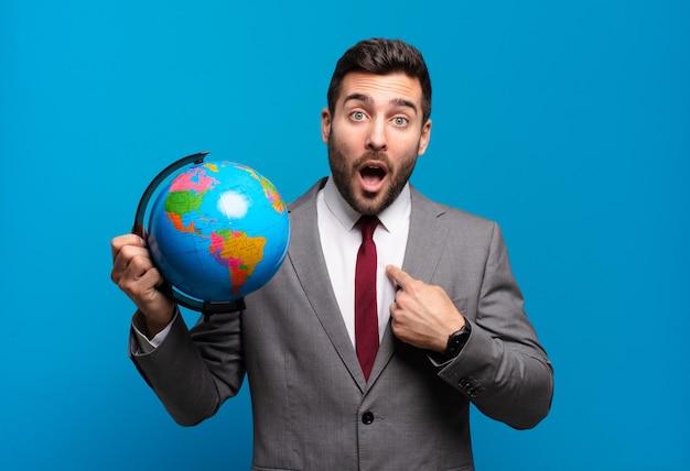 Jeune homme d'affaires à la choqué et surpris avec la bouche grande ouverte, pointant vers l'auto tenant une carte du monde