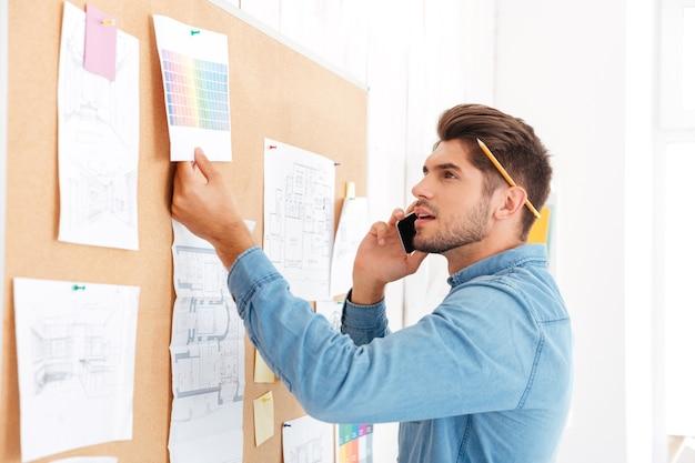 Jeune homme d'affaires concentré décontracté regardant le tableau des tâches du bureau et parlant au téléphone