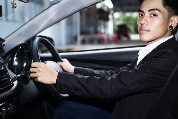 Jeune homme d'affaires conduisant une voiture