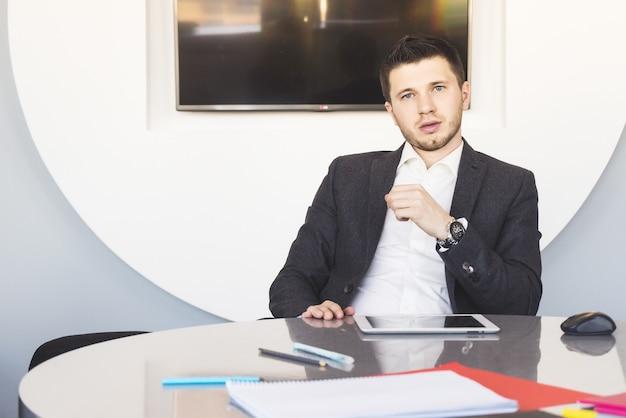 Jeune homme d'affaires confiant au bureau
