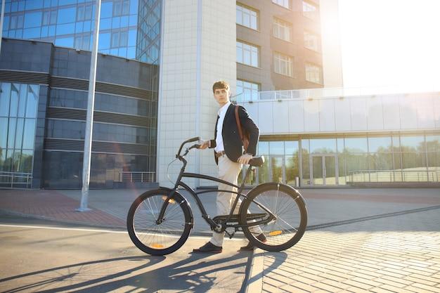 Jeune homme d'affaires confiant marchant à vélo dans la rue en ville.