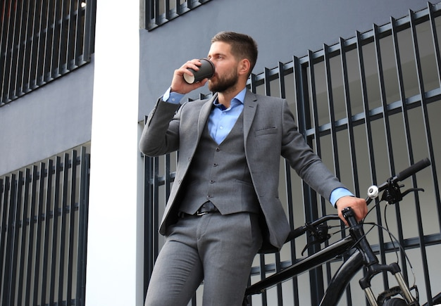 Jeune homme d'affaires confiant avec son vélo buvant du café à l'extérieur.
