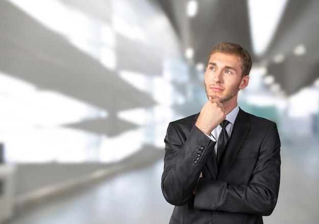 Jeune homme d'affaires confus pensant