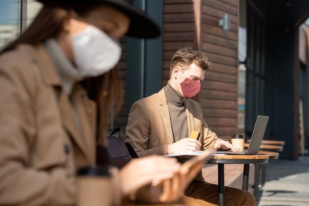 Jeune homme d'affaires contemporain portant un masque de protection et des vêtements de cérémonie tenant une carte de crédit tout en faisant des achats en ligne et en payant l'achat