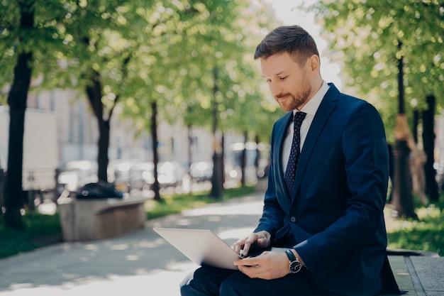 Jeune homme d'affaires en costume bleu parcourant des données et des informations sur son ordinateur portable, surfant sur internet, tout en travaillant à distance sur un projet, assis sur un banc dans un parc de la ville avec des arbres verts le jour d'été