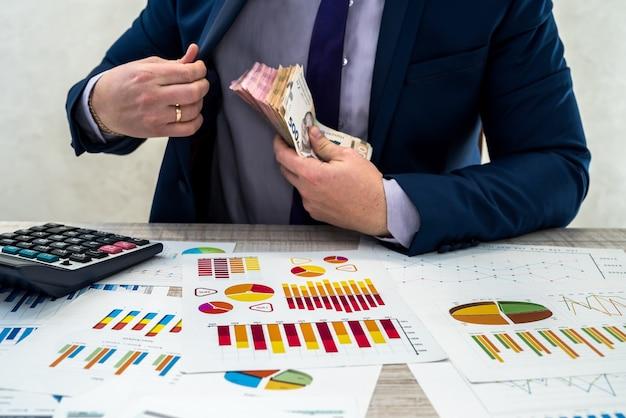 Un jeune homme d'affaires en costume compte l'argent de la hryvnia et travaille avec des graphiques et des documents comme revenu mensuel net. le concept de l'argent est le salaire ou la corruption. travailler au bureau.