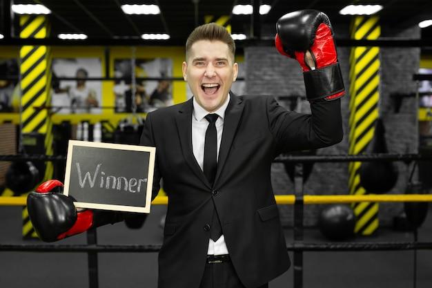 Jeune homme d'affaires en costume dans un ring de boxe avec des gants est titulaire d'un signe avec le gagnant de l'inscription.