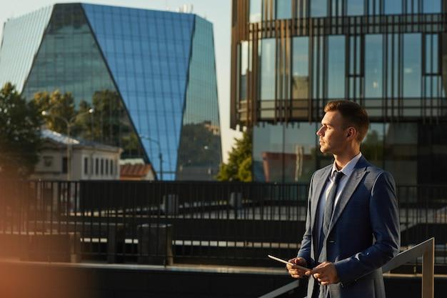 Jeune homme d'affaires en costume formel à la recherche de suite avec un regard pensif debout dans la ville avec des bâtiments modernes