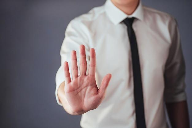 Jeune homme d'affaires en costume montre sa main