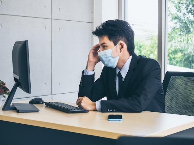 Jeune homme d'affaires en costume portant un masque protecteur travaillant sur ordinateur et pensant avec tension avec un visage fatigué avec un smartphone sur un bureau près d'une immense fenêtre en verre.