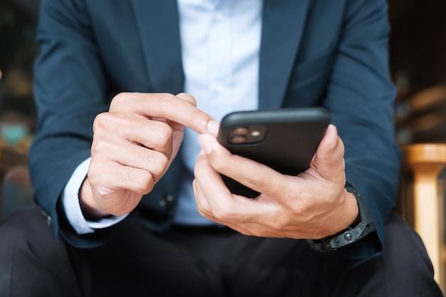 Jeune homme d'affaires en costume tenant et utilisant un smartphone pour les messages sms, homme tapant un téléphone portable à écran tactile au bureau ou au café. concept de réseau d'entreprise, de style de vie, de technologie et de médias sociaux
