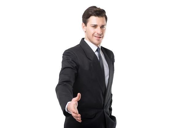 Jeune homme d'affaires en cravate et costume noir étend sa main, isolé sur blanc