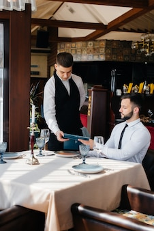 Un jeune homme d'affaires dans un bon restaurant examine le menu et passe une commande à un jeune serveur dans un tablier élégant. service clients.