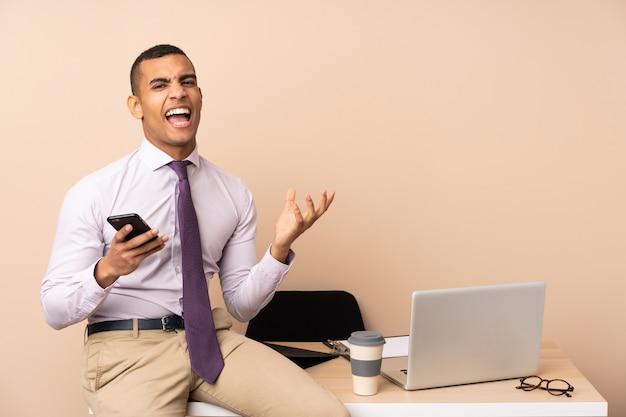 Jeune homme d'affaires dans un bureau mécontent et frustré par quelque chose