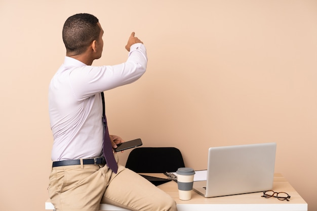 Jeune homme d'affaires dans un bureau pointant vers l'arrière avec l'index