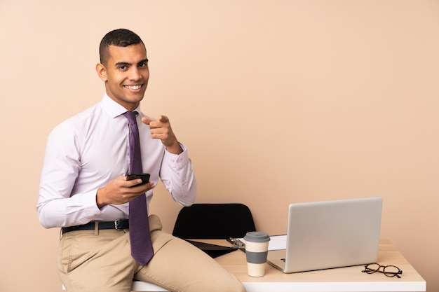 Jeune homme d'affaires dans un bureau pointe le doigt vers vous
